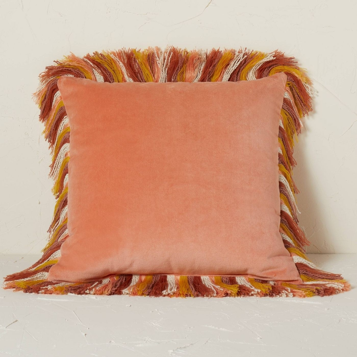 the terracotta pillow with multicolored fringe