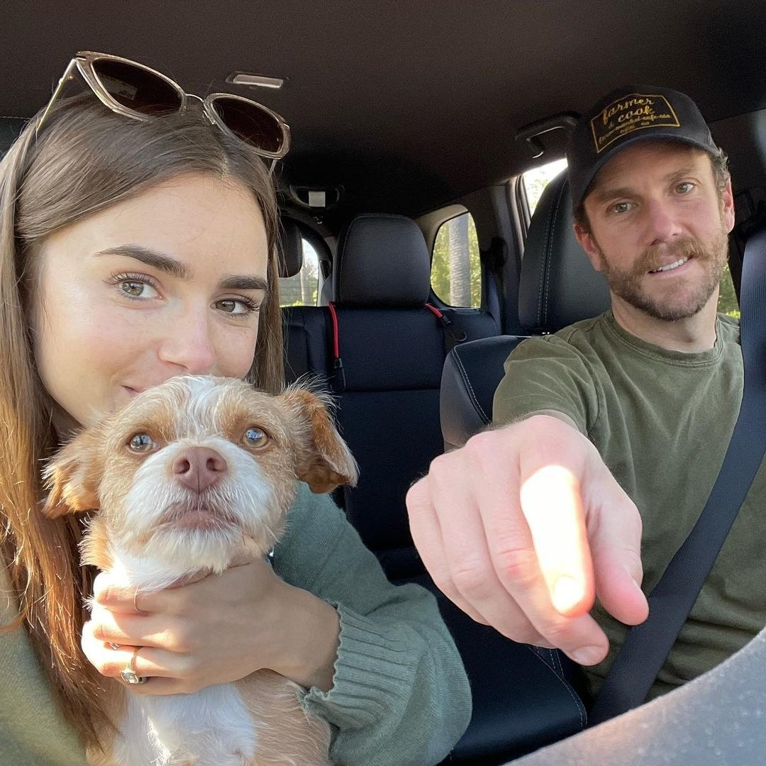 Lily, holding a dog, with Charlie in a car