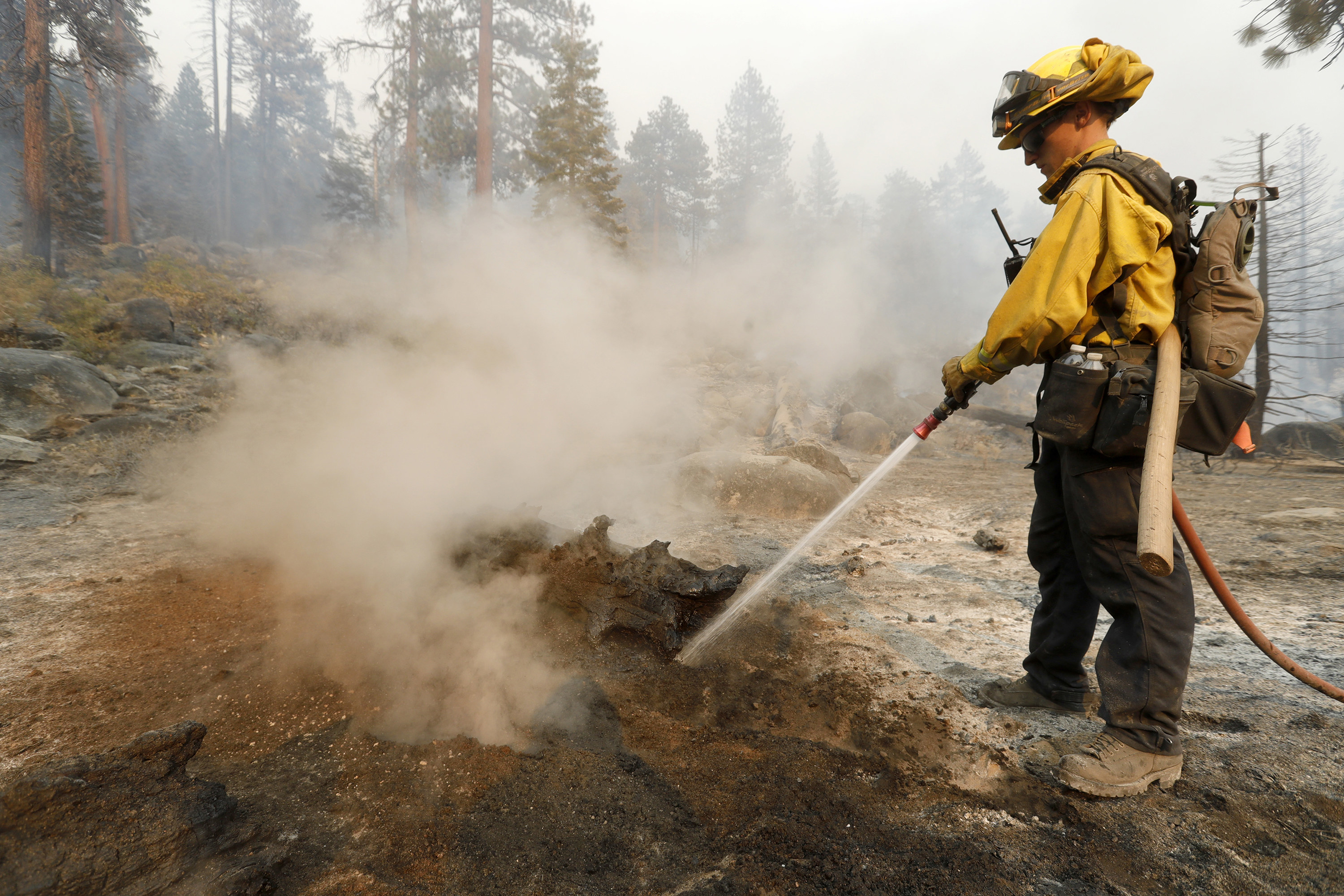 A firefighter points a hose at the ground, where smoke arises from smoldering patches