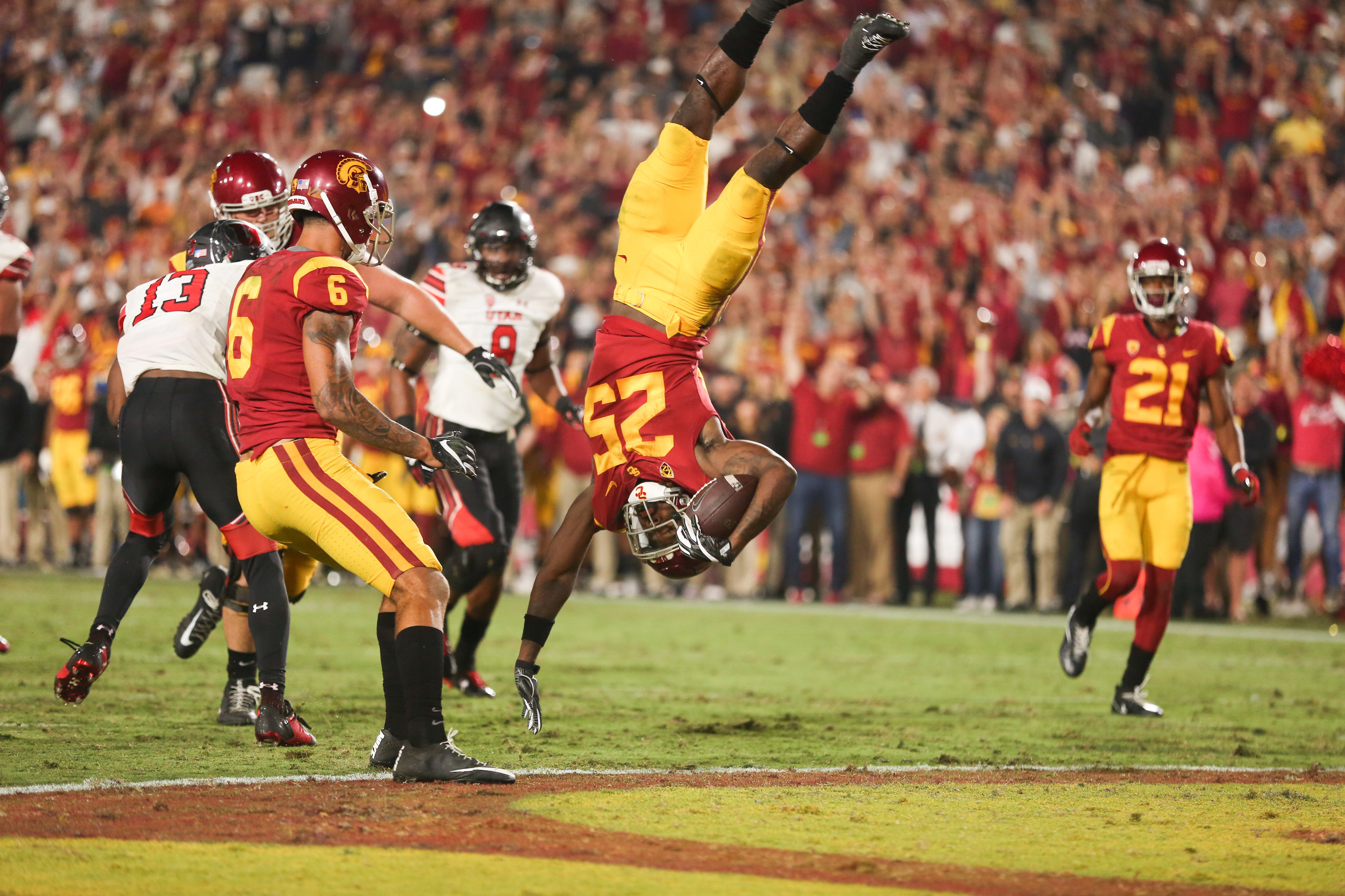 A football player is seen upside down holding a football at a USC game