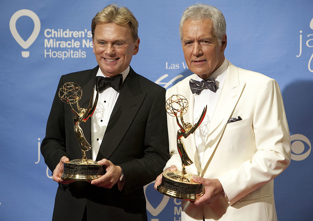 Pat Sajak posing andAlex Trebek standing together and each holding an Emmy Award