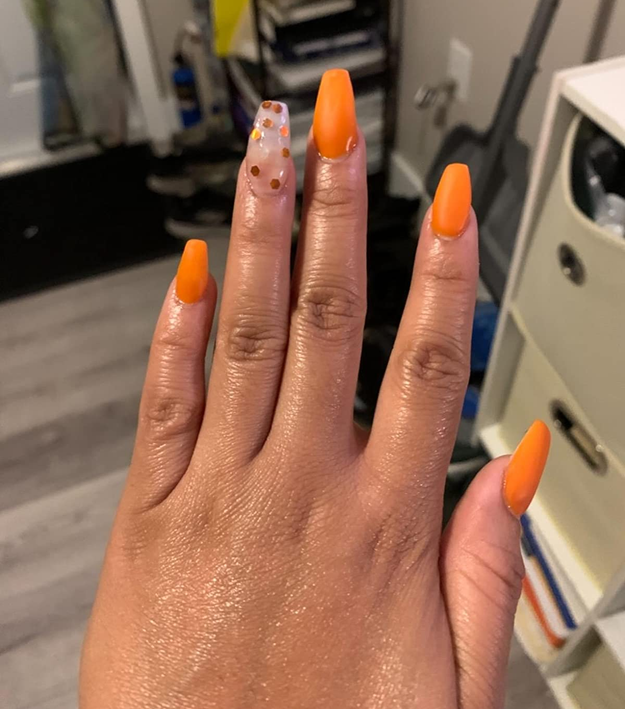 Reviewer photo of their nails in a bright orange color and the ring fingernail in a transparent style with orange polka dots