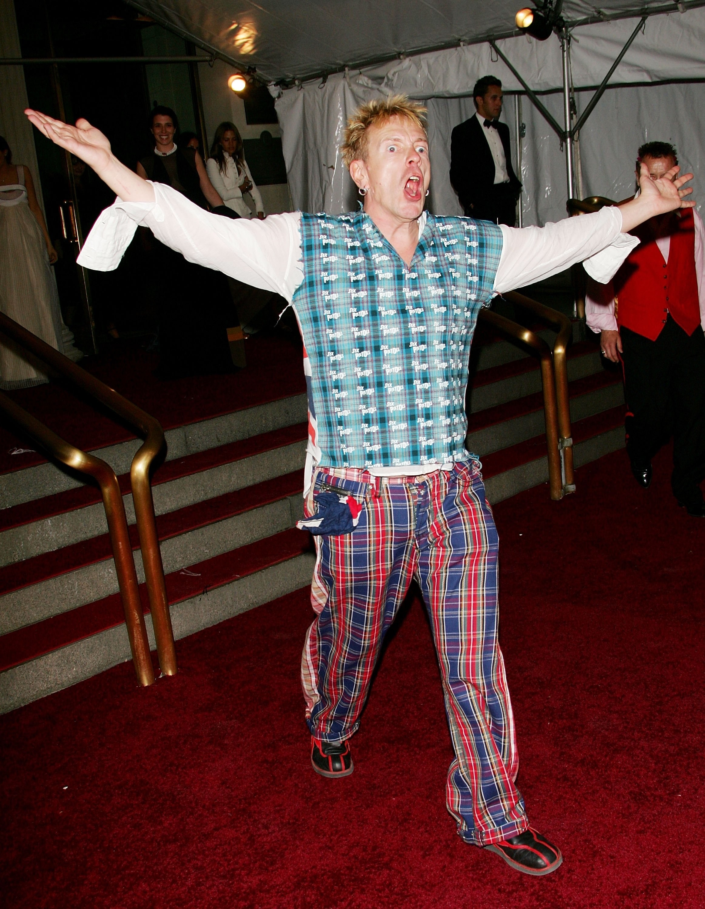 John Lydon screaming with his arms waving in the air