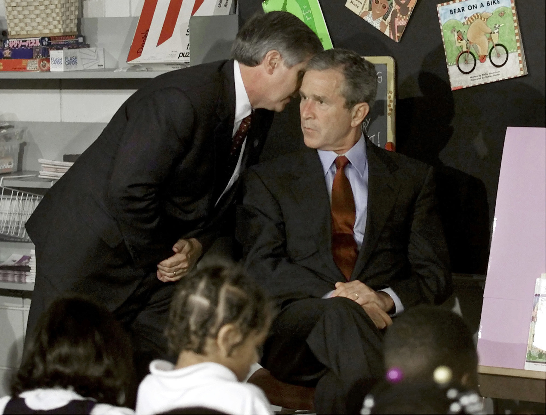 President George W. Bush looking very serious while another man in a suit whispers in his ear in a children's classroom