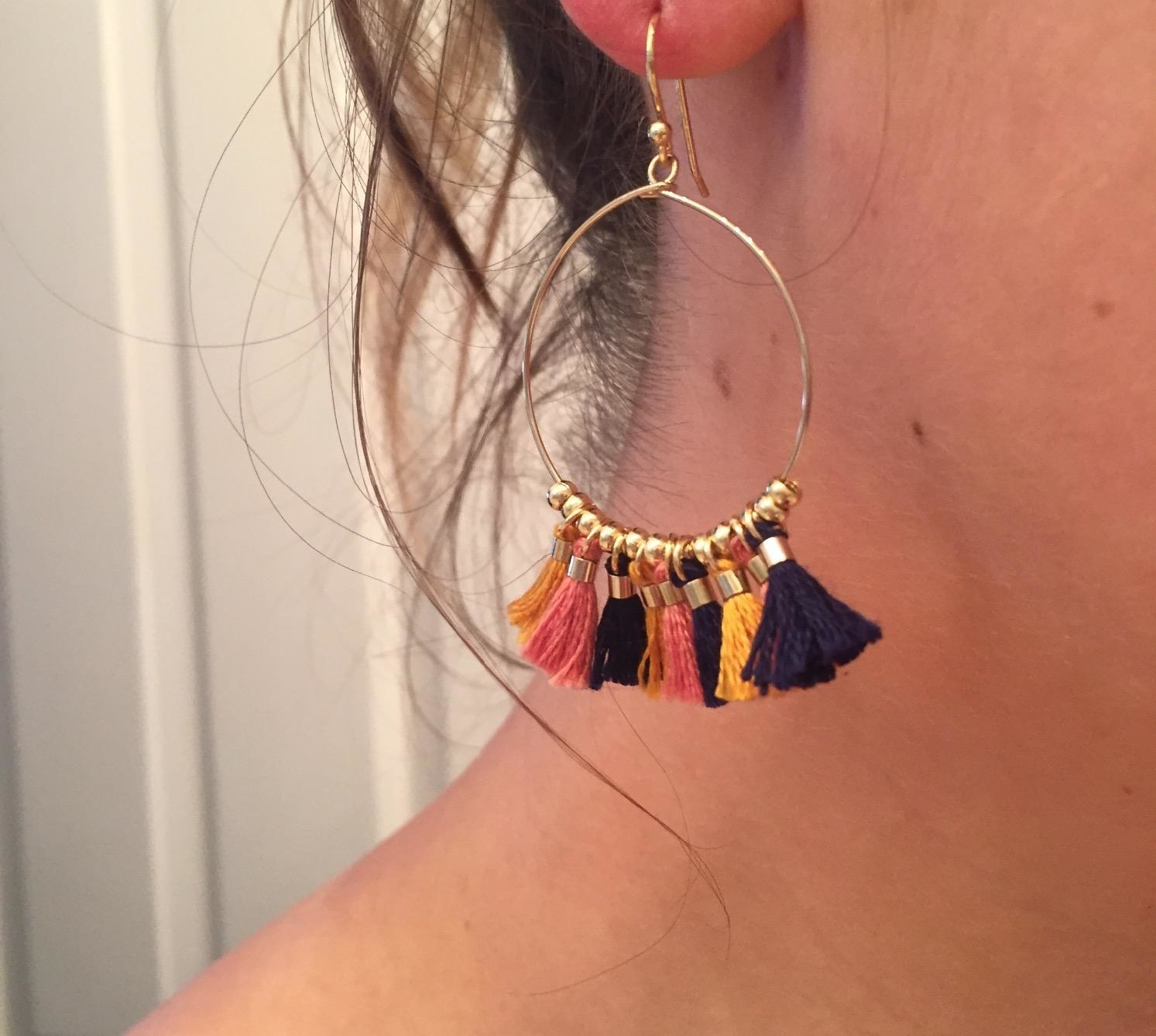 the autumn leaf tassel earring hanging from a reviewer's ear