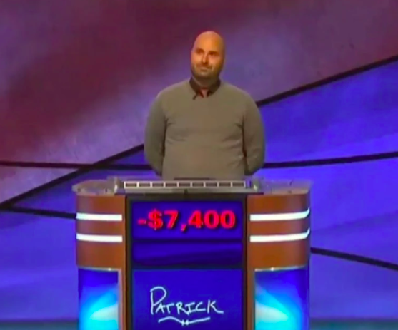 Patrick Pearce standing in front of a podium reading -$7,400