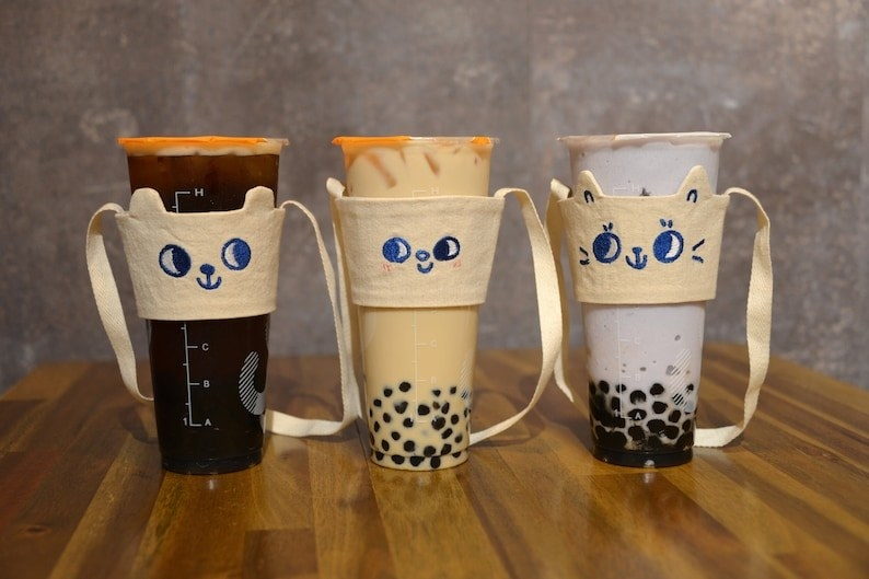 the canvas cupholders with straps and cute embroidered faces