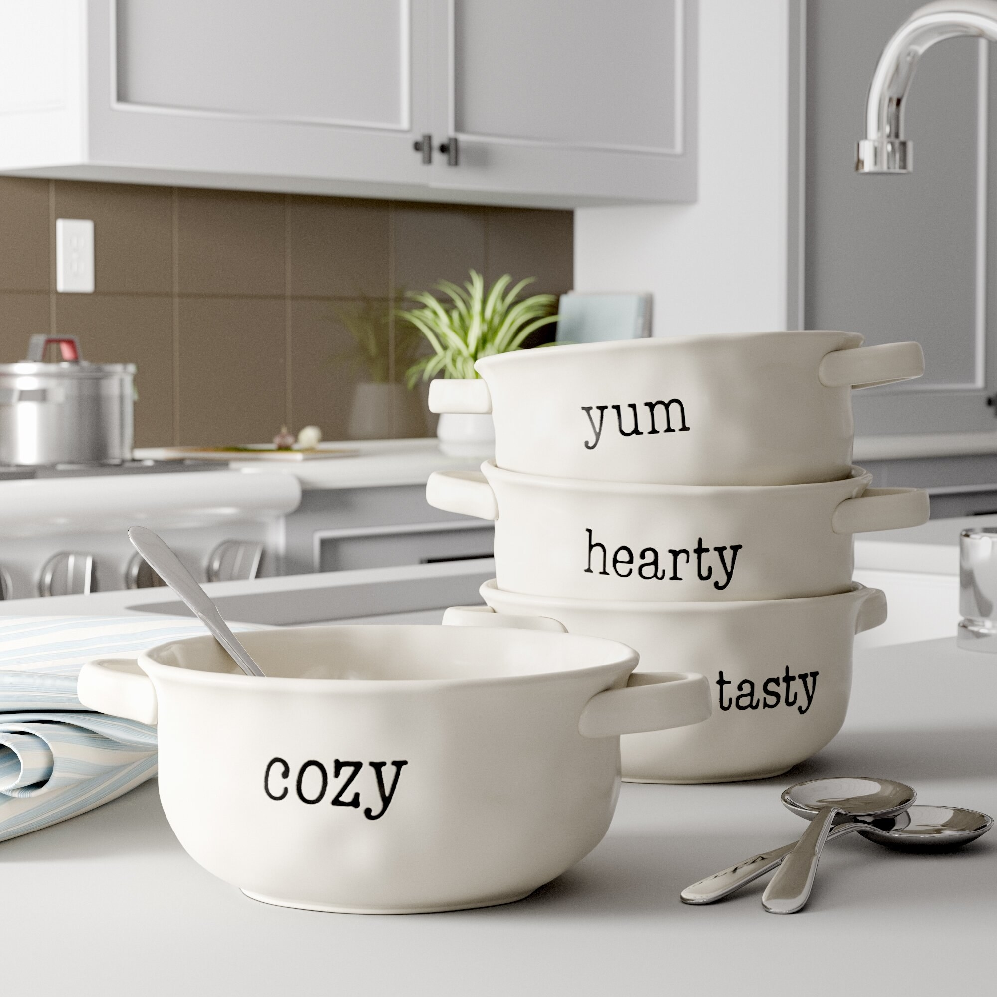 """the four white bowls with the words """"cozy,"""" """"yum,"""" """"hearty,"""" and """"tasty"""" engraved on them"""