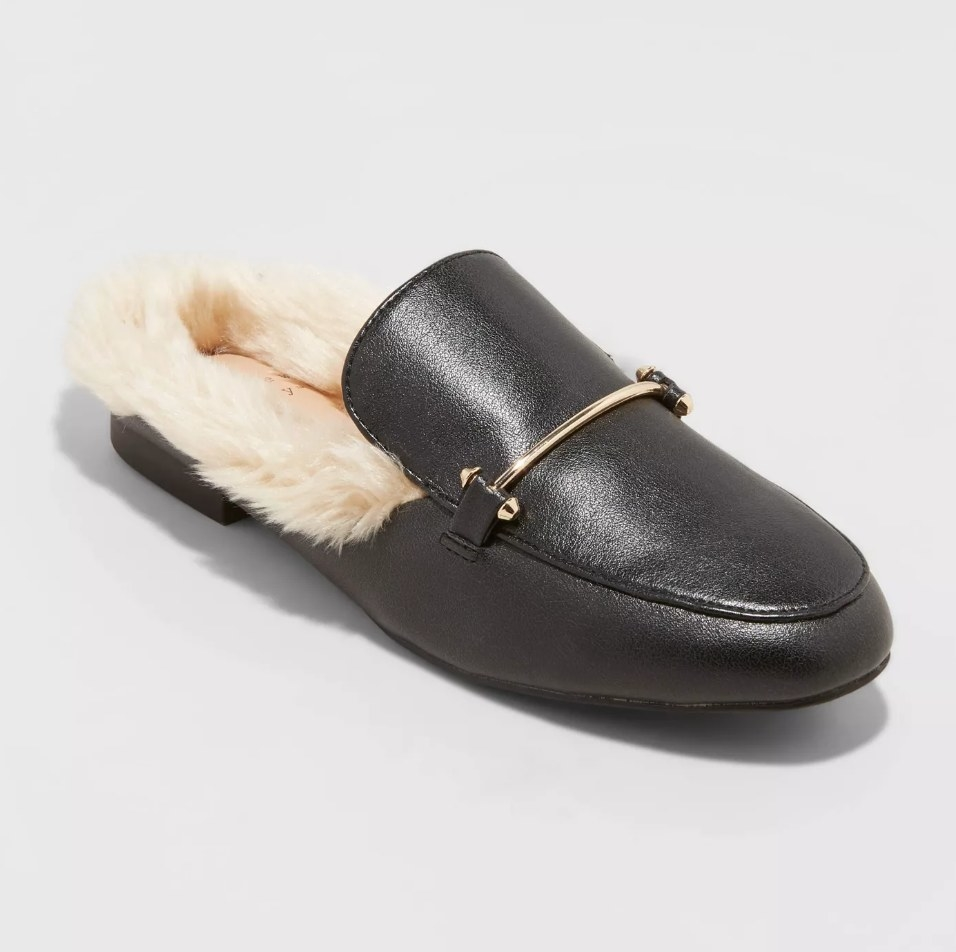 Faux leather black mule with gold bar across foot and beige faux fur inside