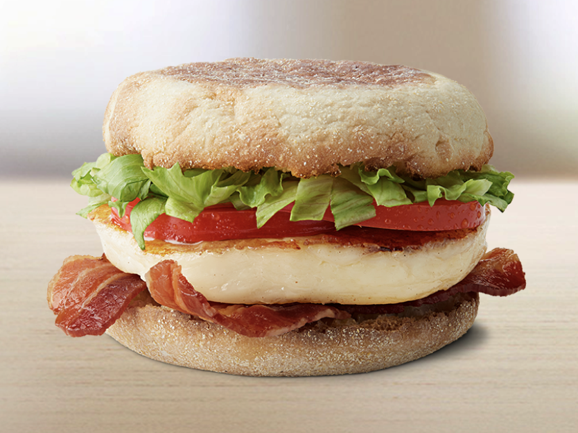 english muffin topped with grilled halloumi, bacon, tomato, and lettuce