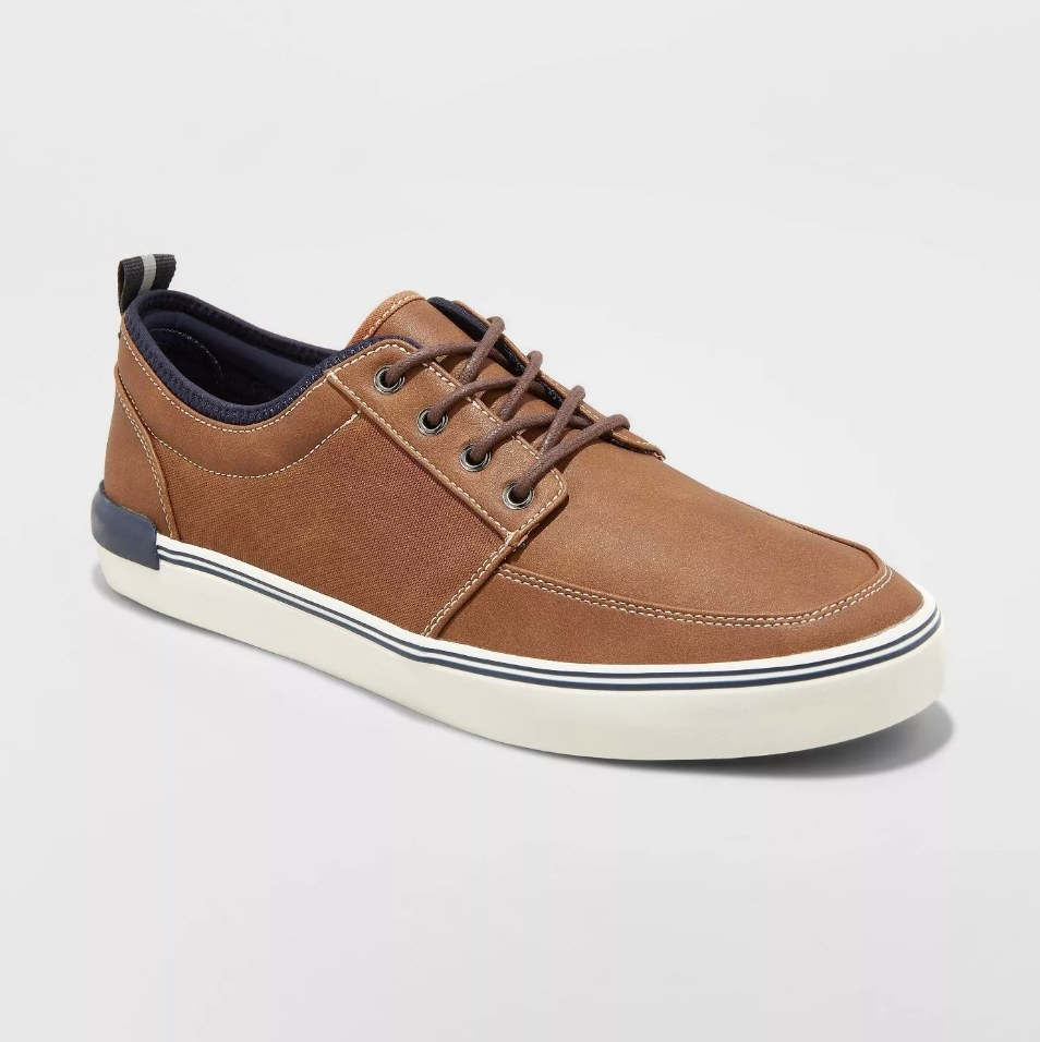 Brown sneaker with white stitching and sole, navy detailing on the interior