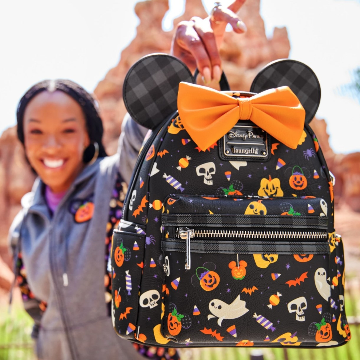A black backpack with orange pumpkins and ghost print, with orange bow and black ears