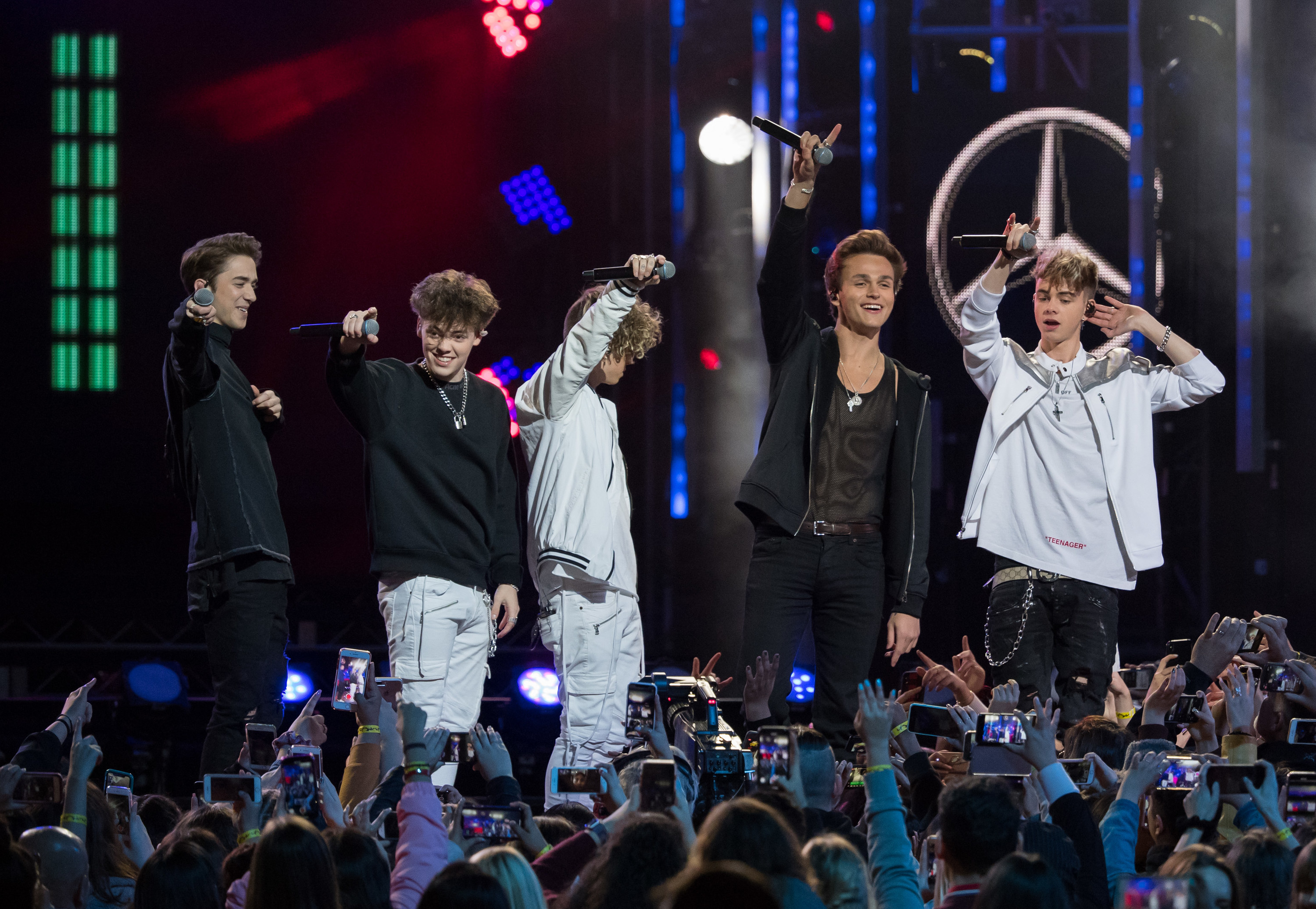 The band smile and hold their microphones in the air on stage
