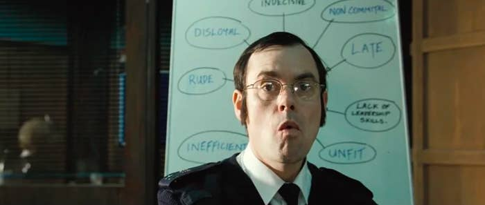 There are thought bubbles on a whiteboard in the background that are framed around a police officer, so the words, like rude and late, look to be about him