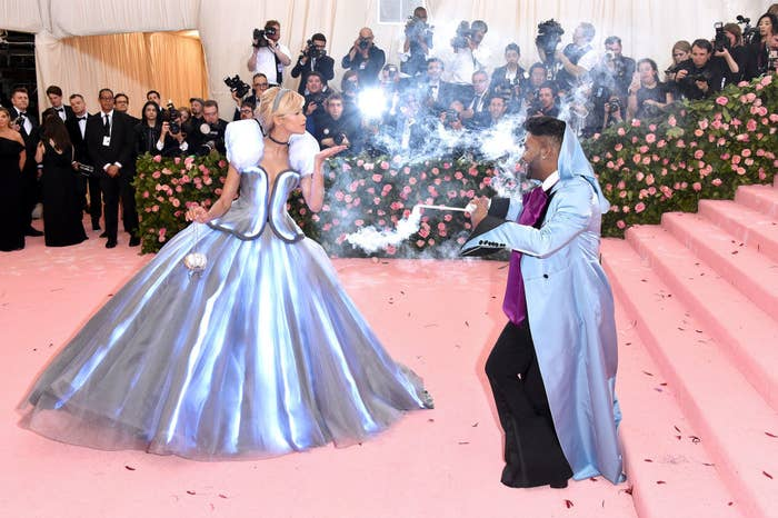 Law Roach waving a wand at Zendaya to illuminate her dress on the red carpet