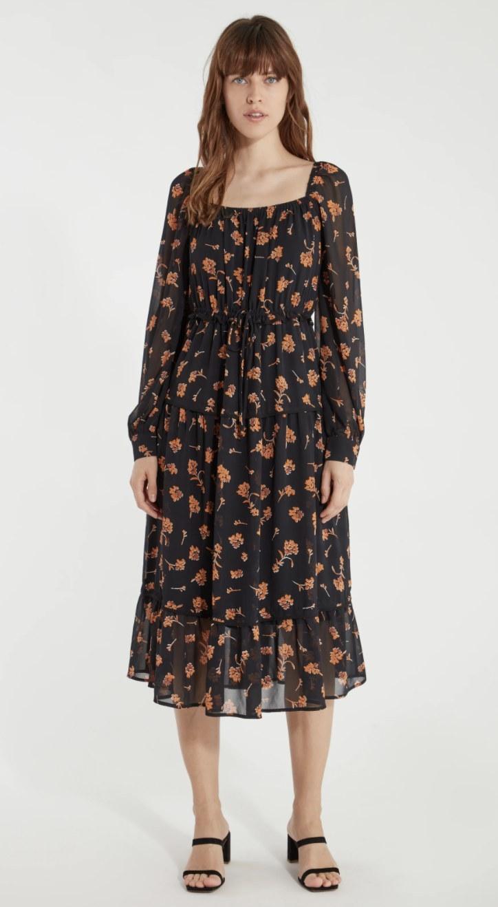 model wearing black and orange floral dress