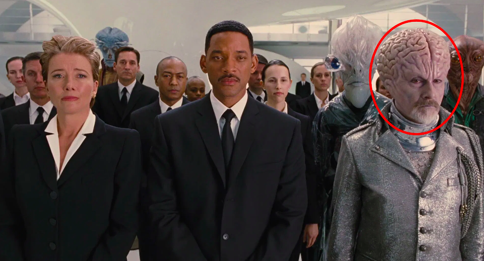 Rick Baker in full makeup next to Will Smith and Emma Thompson in a scene