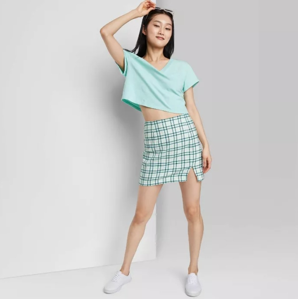a model wearing the skirt in blue plaid