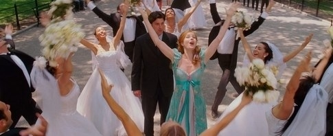 Giselle sings in Central Park surrounded by people in wedding outfits