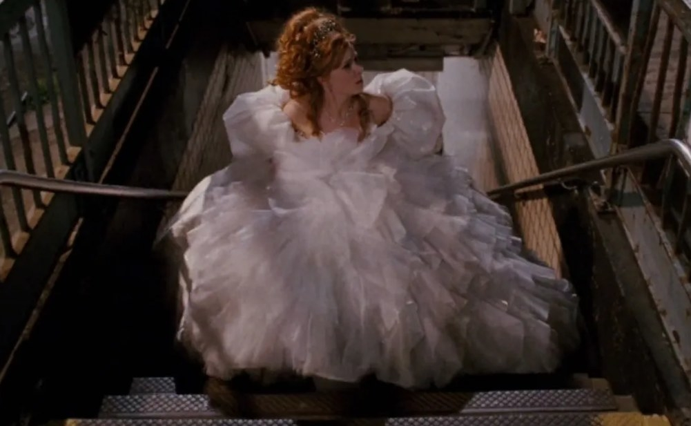 Giselle holds her large white dress and walks up subway stares