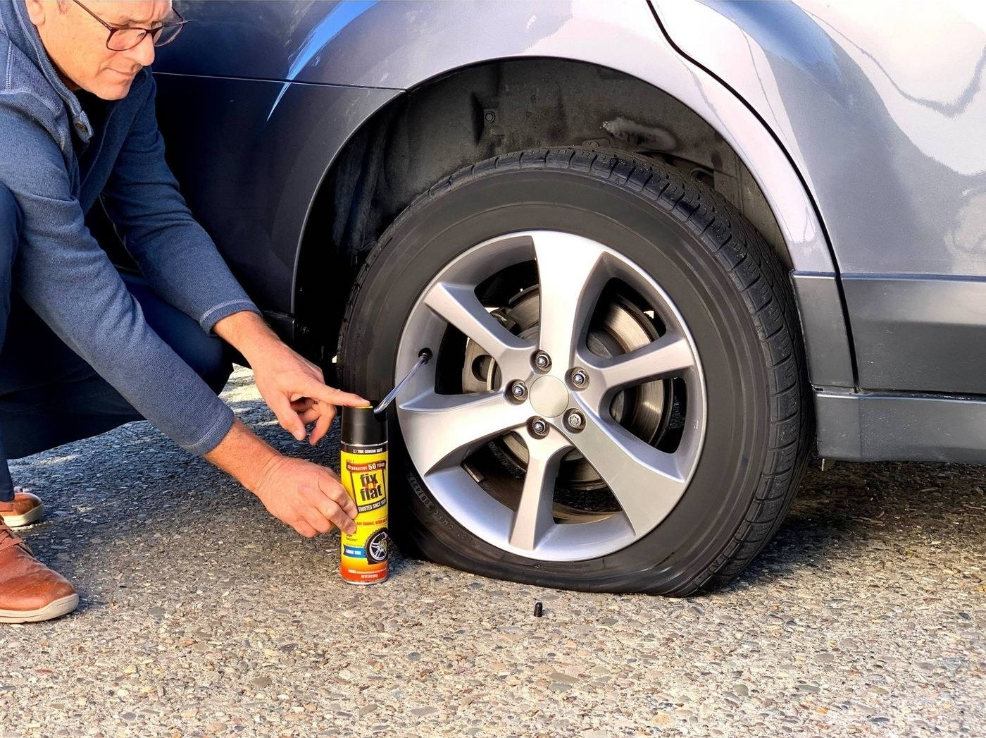 a person using the fix a flat to inflate the tire