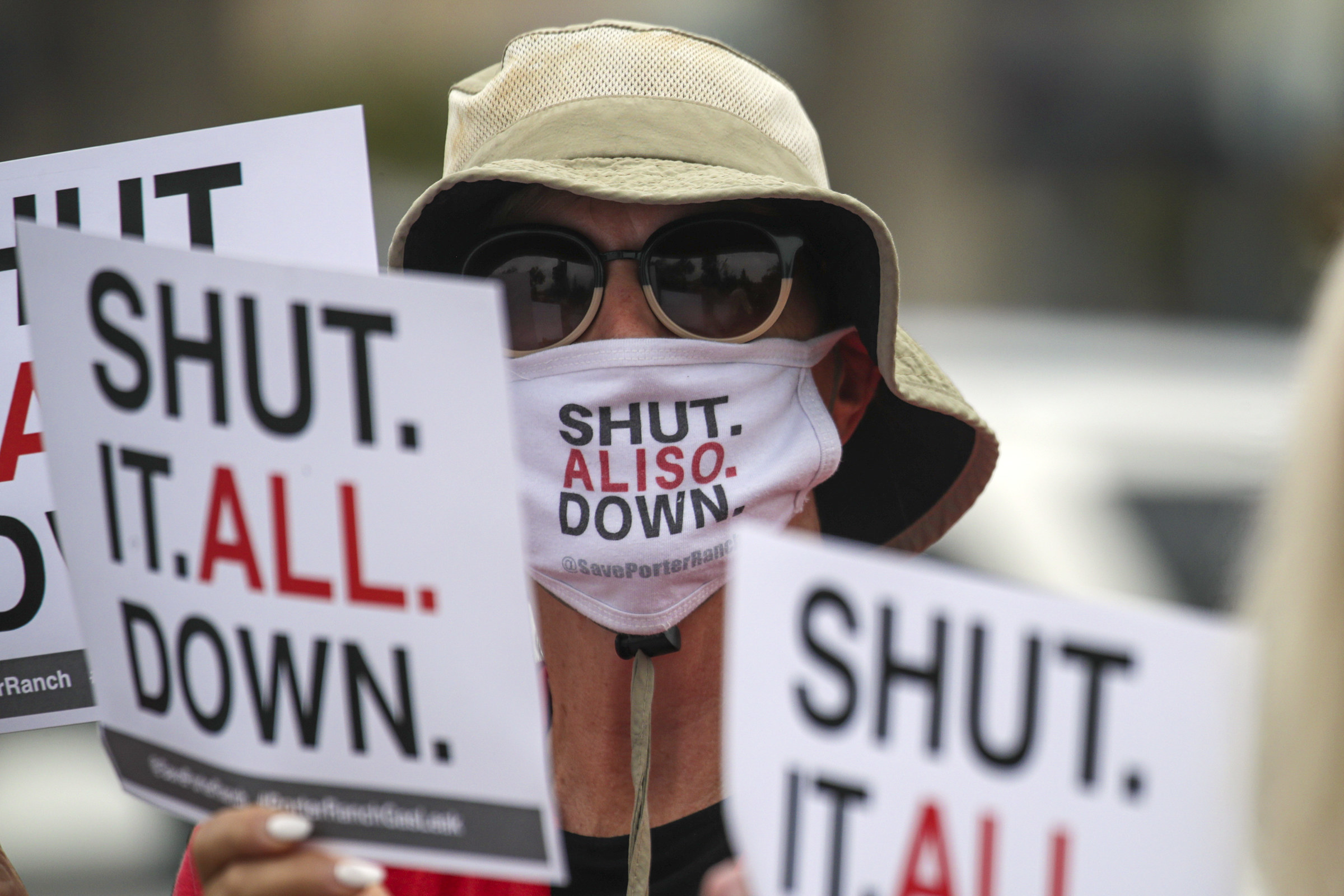 """Person wearing a mask with """"Shut Aliso Down"""" on it and signs saying """"Shut It All Down"""""""