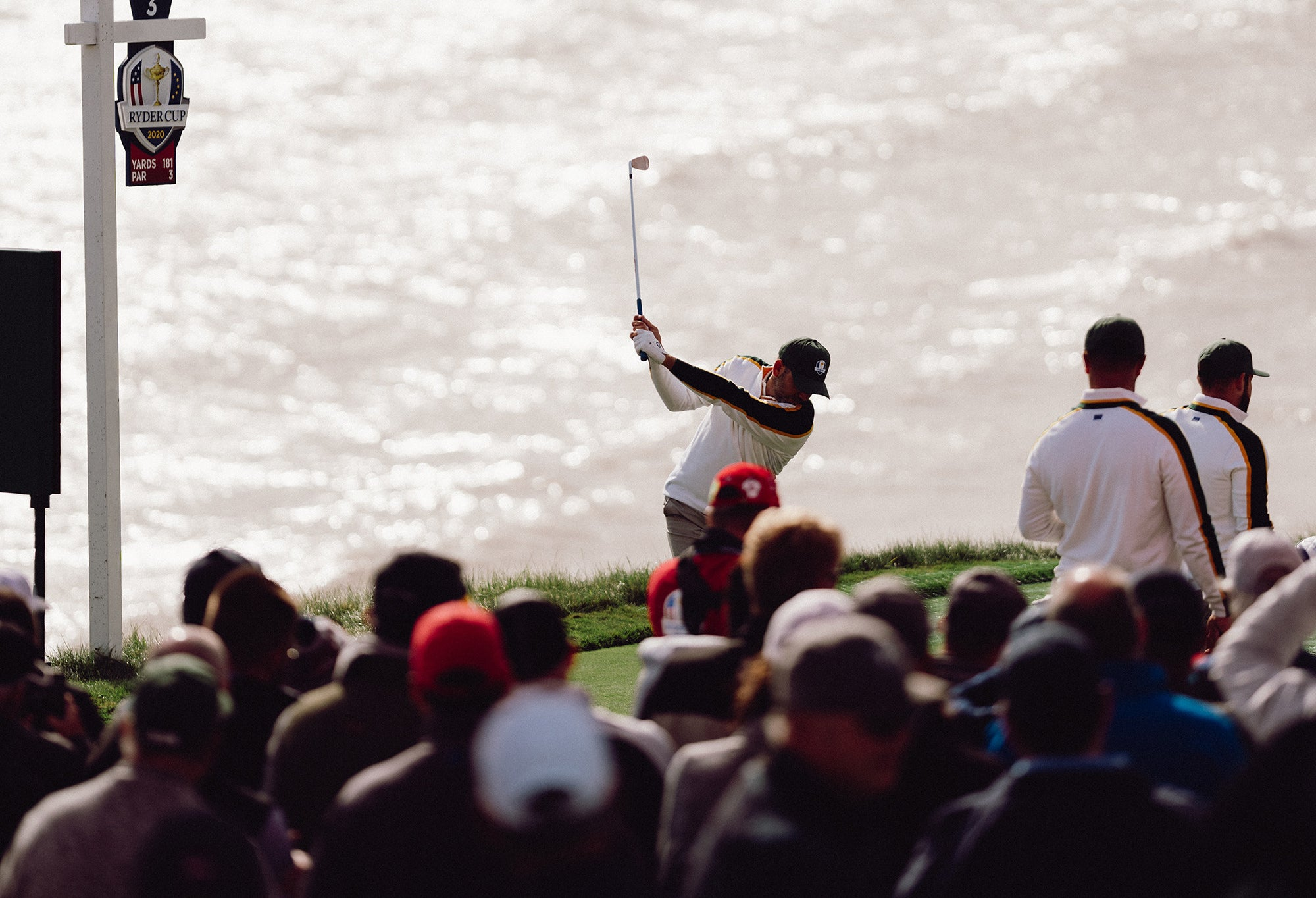 Person playing golf with crowd looking on