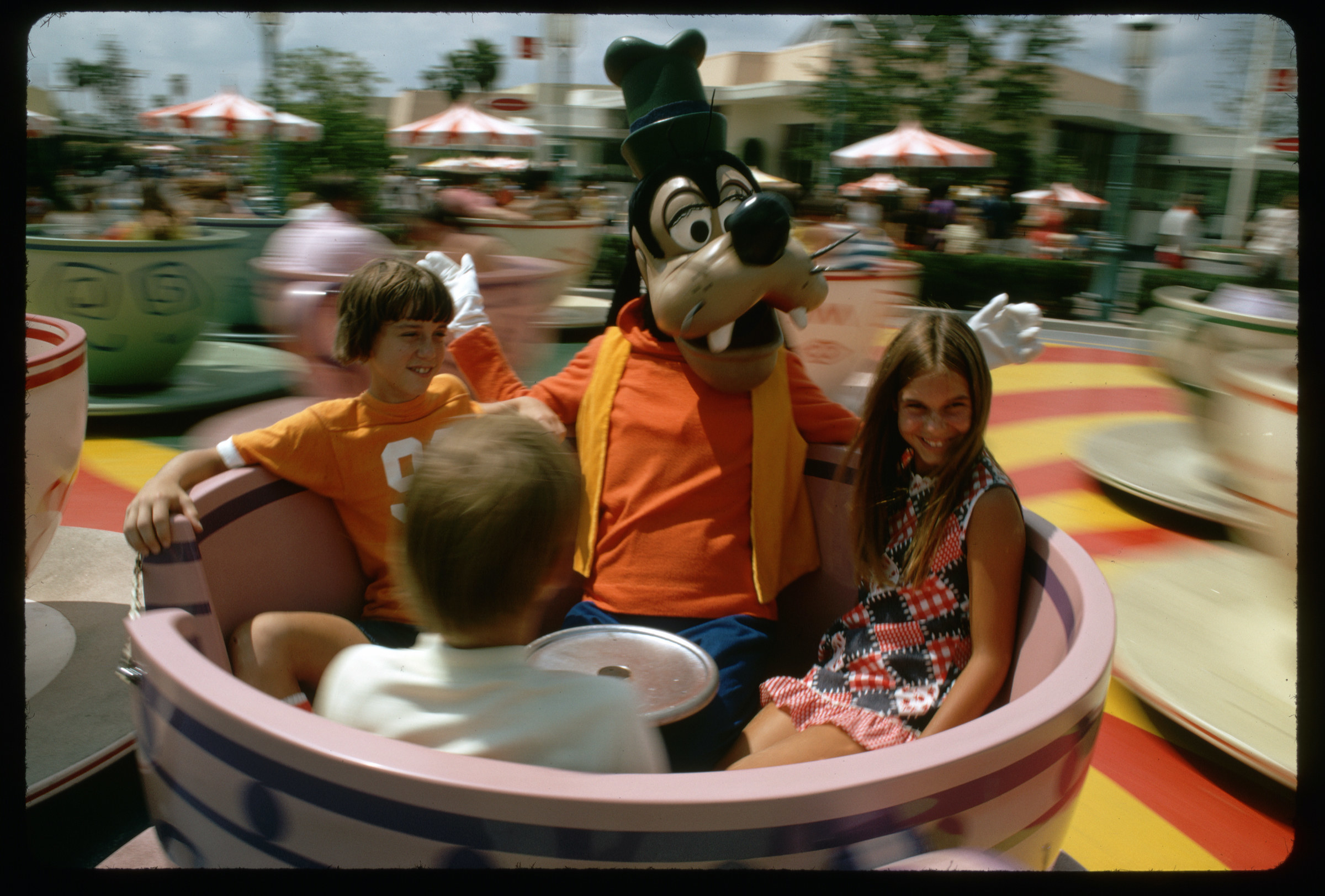Goofy rides the Mad Tea Party Ride with children in the Magic Kingdom at Walt Disney World in 1972