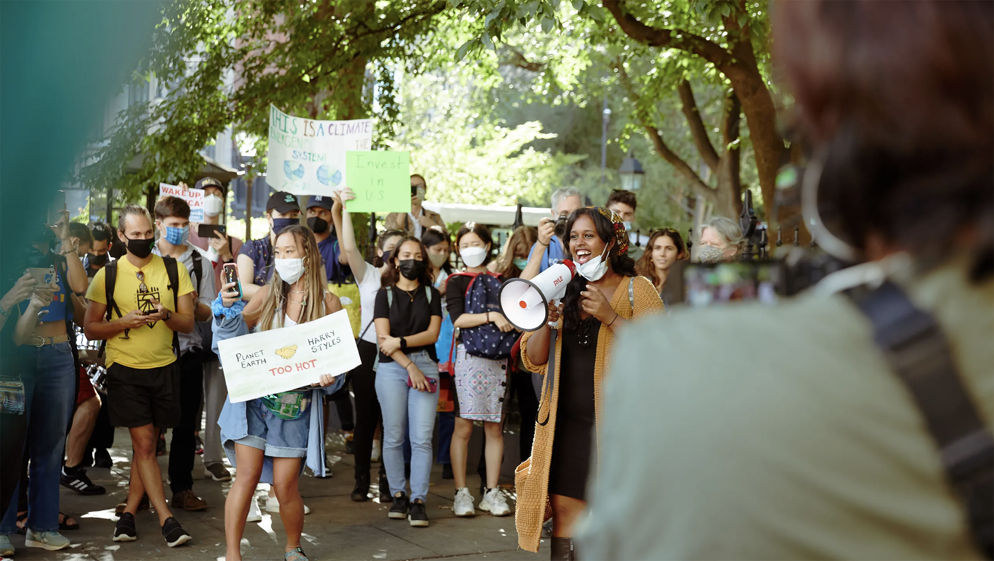 Crowd of people, most wearing masks, hold up signs, with one person in the foreground with a loudspeaker