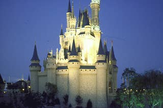 Cinderella's Castle lit up at night and reflected in an artificial stream at Disney World