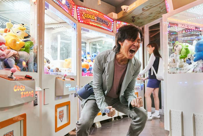 A man standing between claw machines screams, with his fists clenched, in this screengrab from Squid Game
