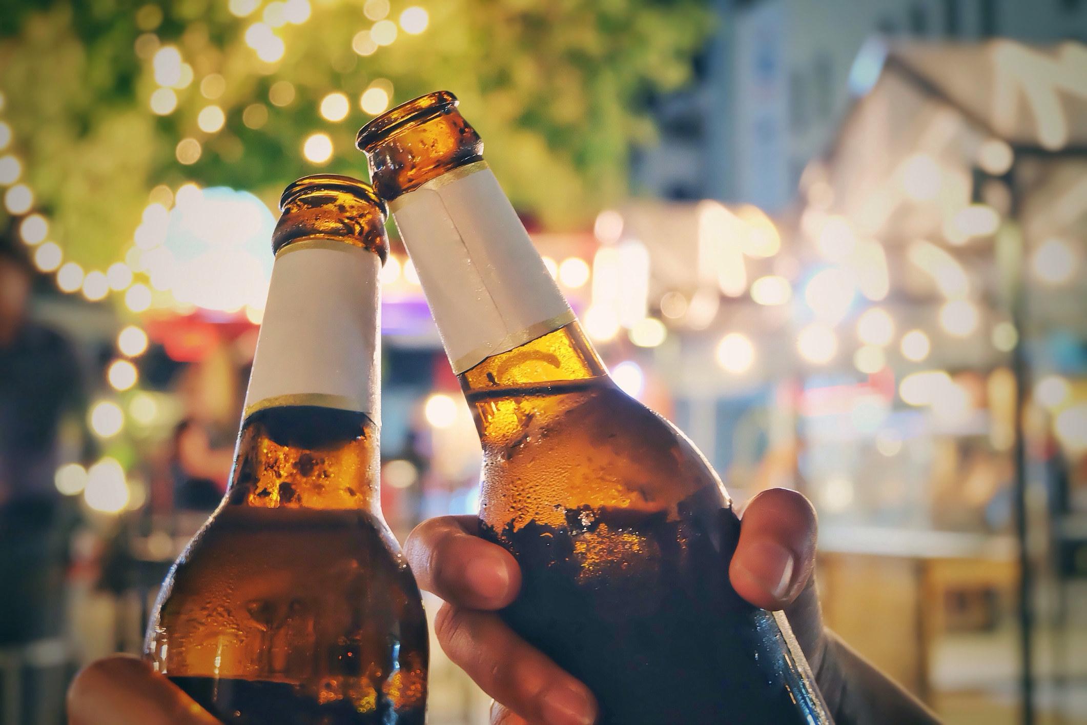 Two beer bottles getting clinked together