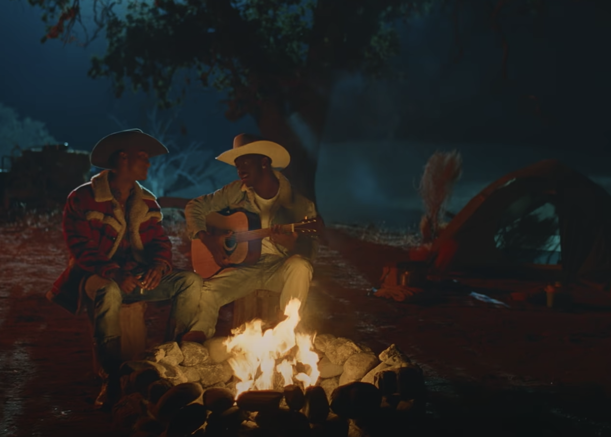 A scene from the That's What I Want video with Lil Nas X playing the guitar as he and Yai sit at a campfire