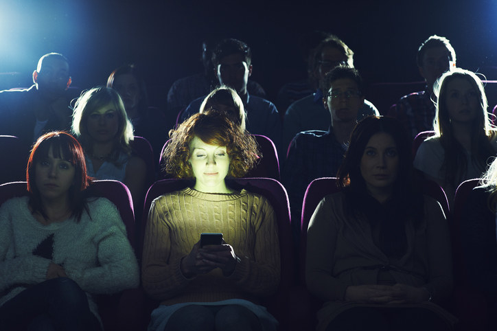 A person staring at their phone in a dark movie theater as other people who are trying to watch the film