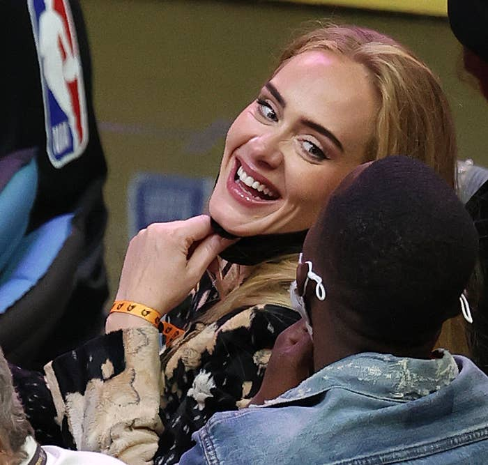 Adele smiles at someone behind her at a basketball game