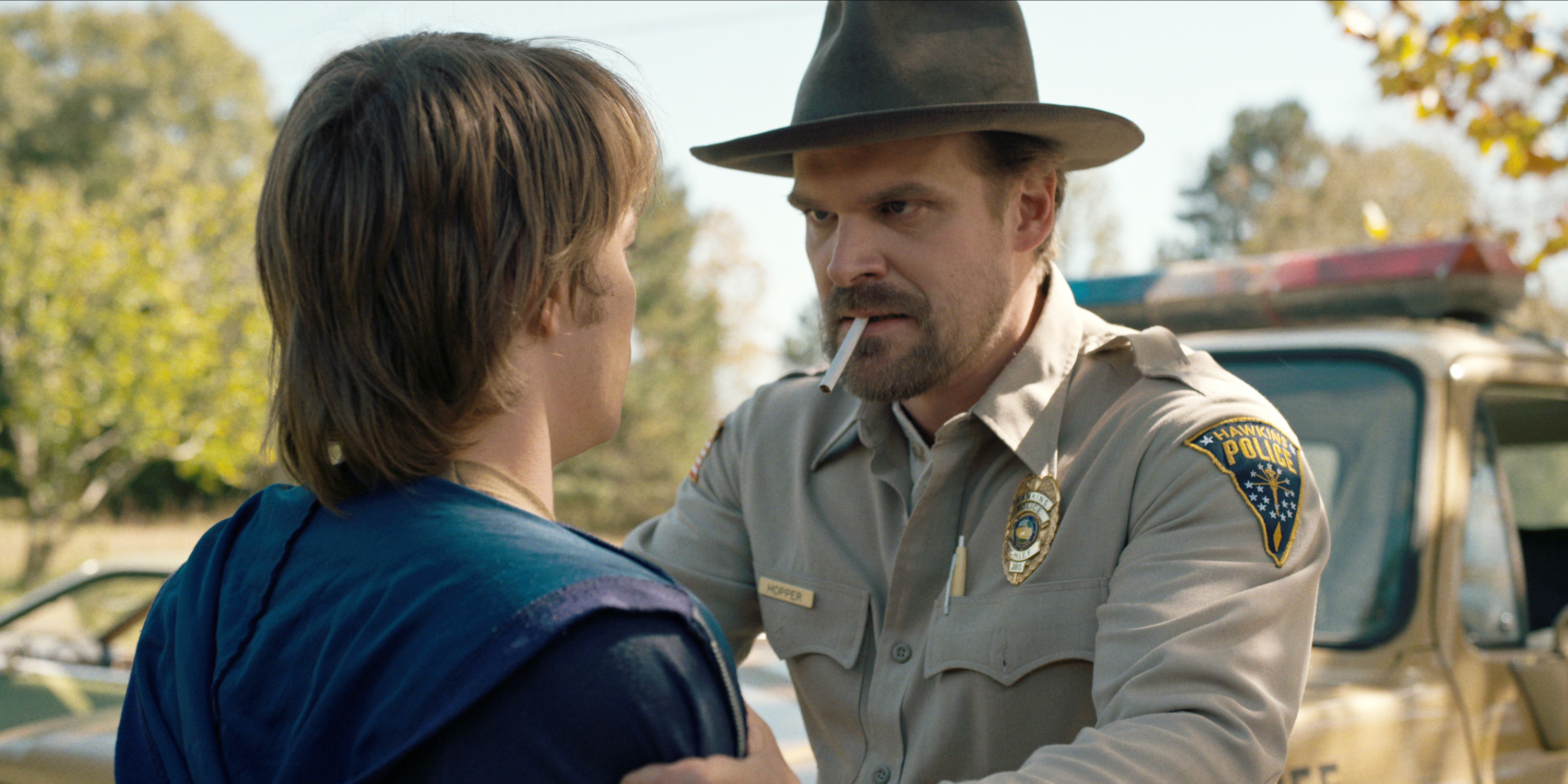 David's Stranger Things character holding onto someone as a cigarette hangs from his mouth