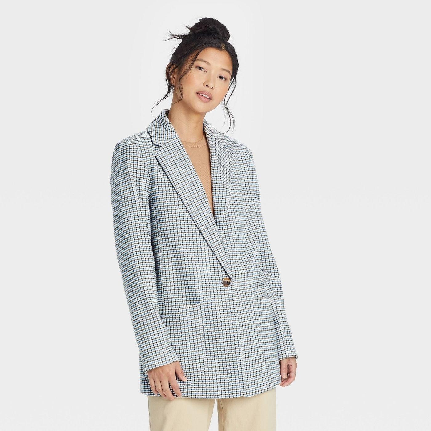a woman wearing a plaid blazer