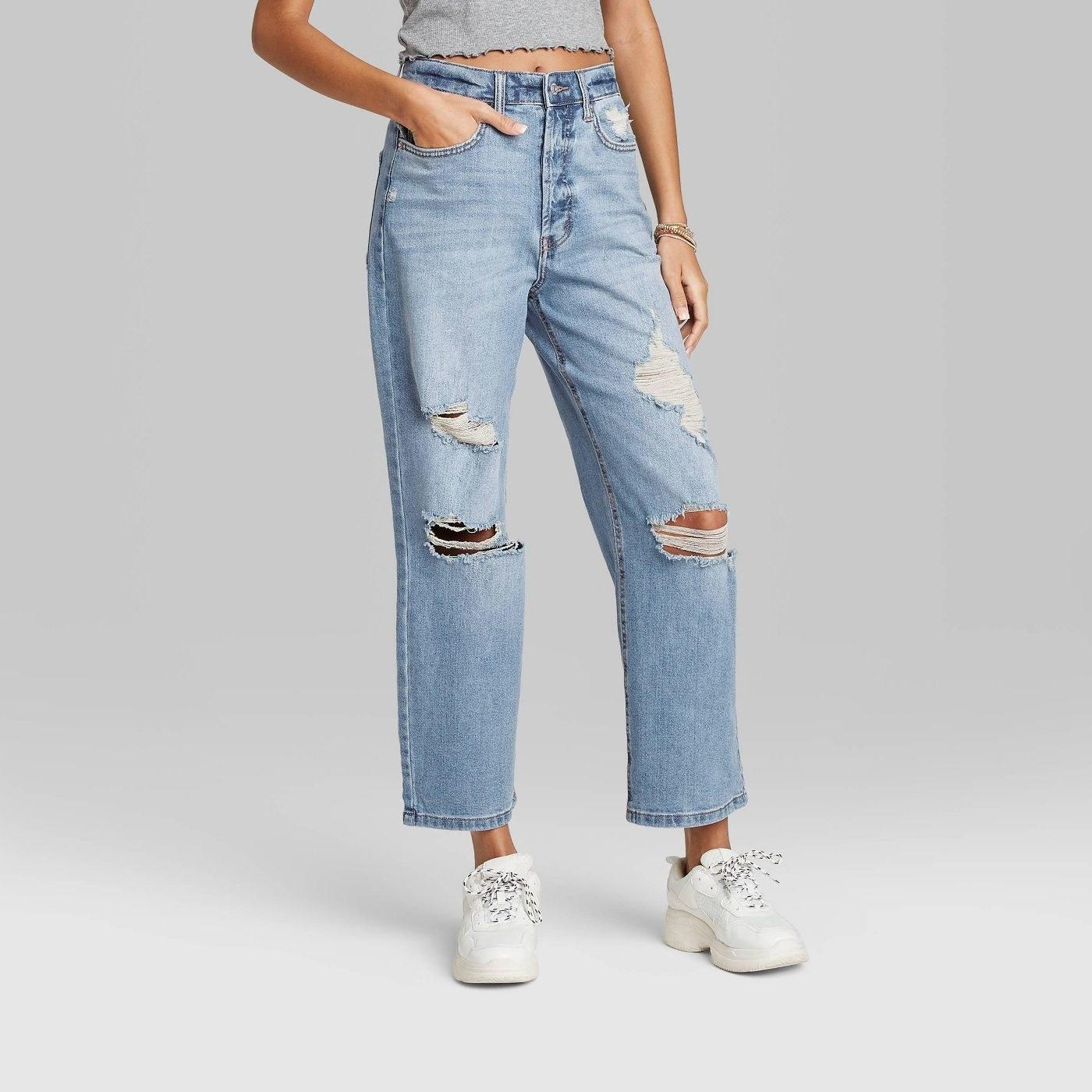 a woman wearing ripped boyfriend jeans