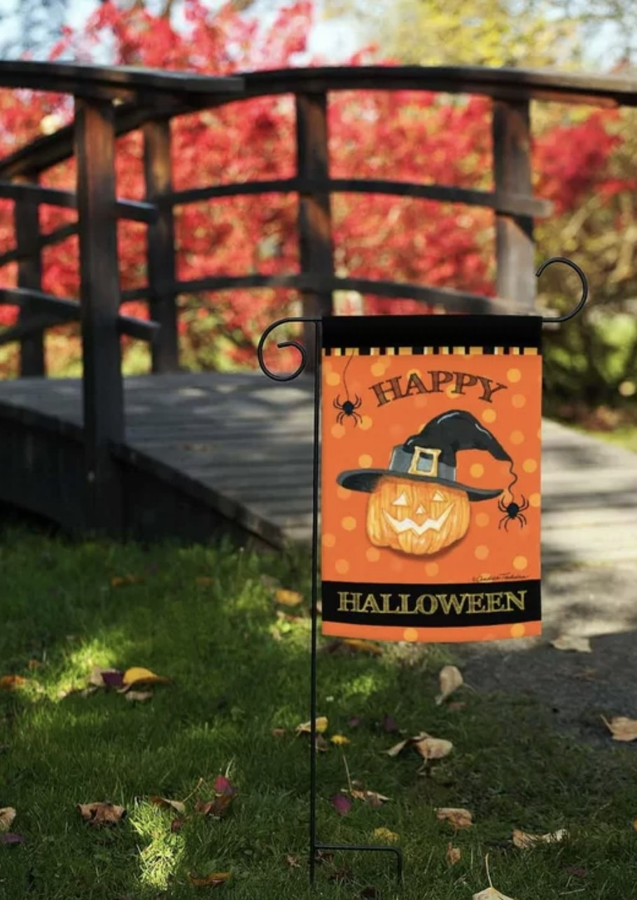 """The orange flag with black borders says """"HAPPY HALLOWEEN"""" and has a jack-o-lantern wearing a witch hat and with spiders"""