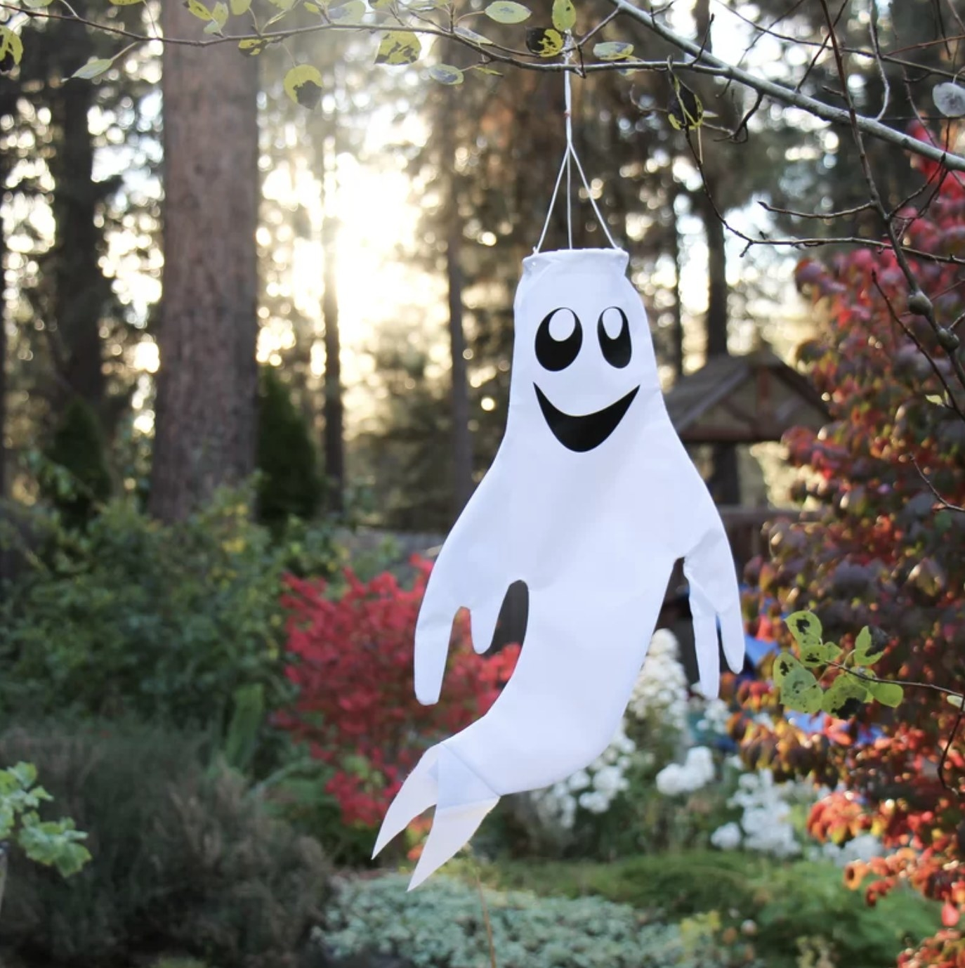 The white windsock ghost floats in the wind while grinning
