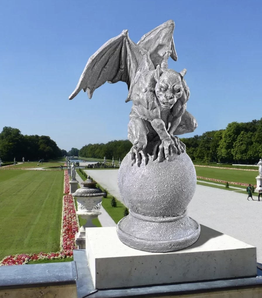 The grey gargoyle sits atop of a spherical mound with large wings and a muscular build