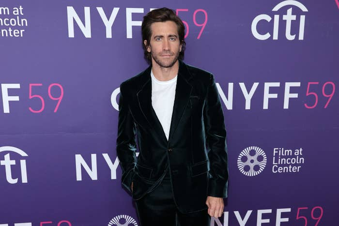 Jake Gyllenhaal with his hand in his pocket while wearing a velvet suit at a red carpet event