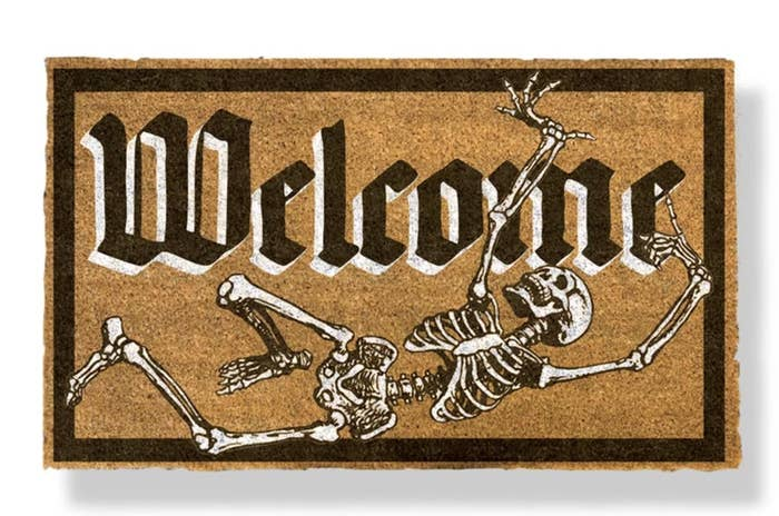 """The rectangular mat says """"Welcome"""" in old black font with white borders and a black and white skeleton below"""