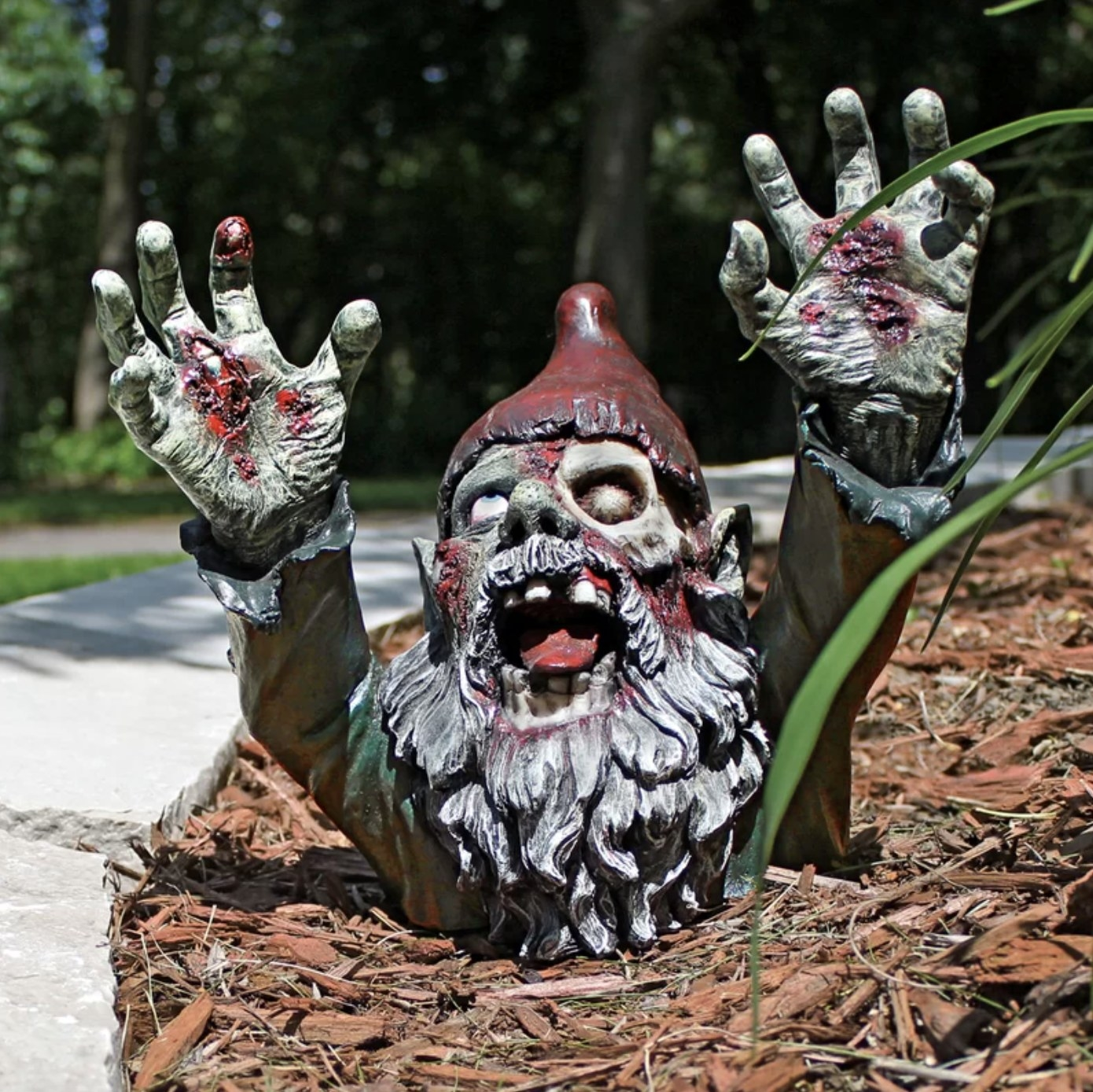 The gnombie is reaching upward with their hands outstretched and mouth opened wide and blood and peeling skin