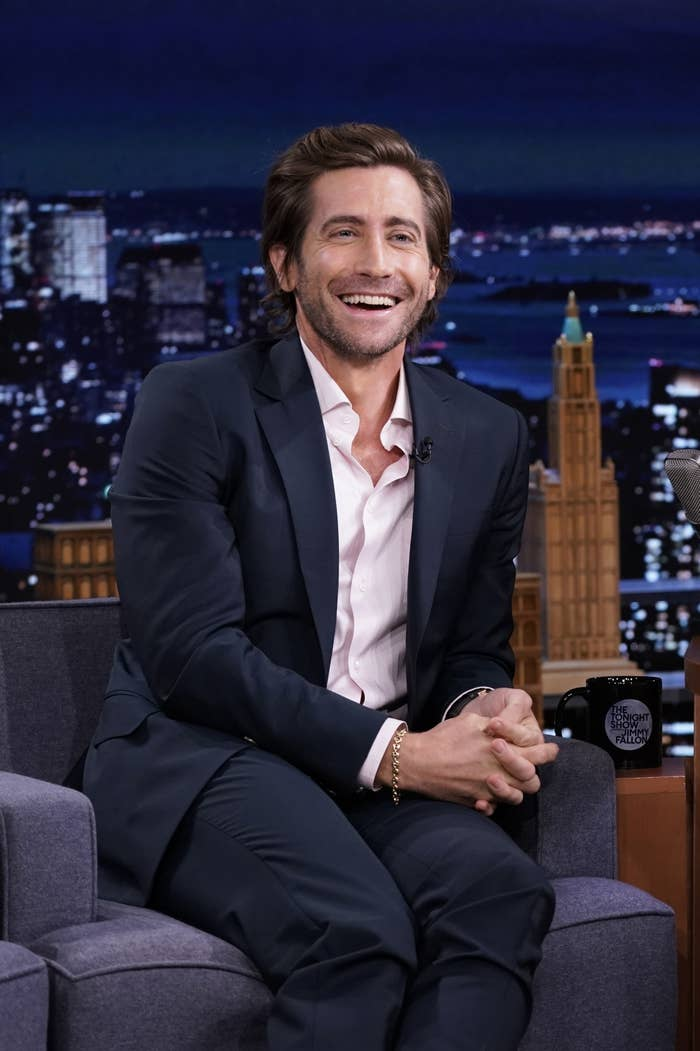 Gyllenhaal smiles while sitting on a chair