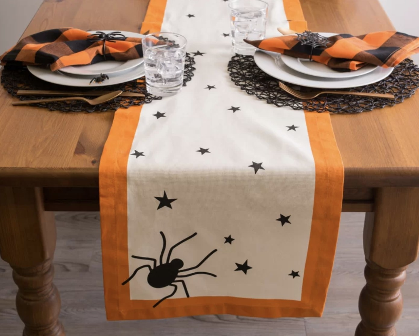 The table runner is all white with an orange border and one large black spider and many mini black stars