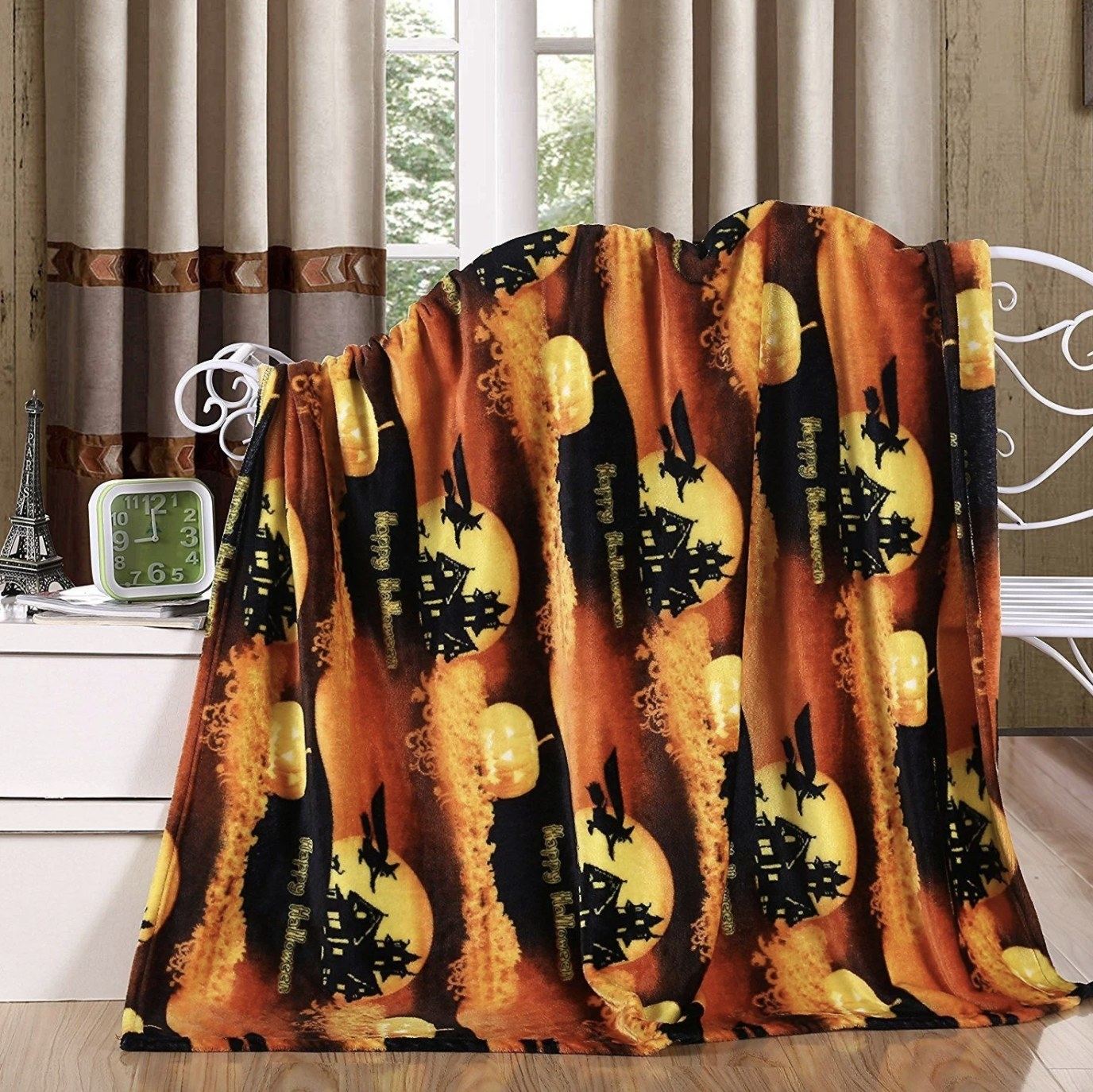 The orange, brown, black and yellow blanket has prints of a moon, haunted house and a flying witch