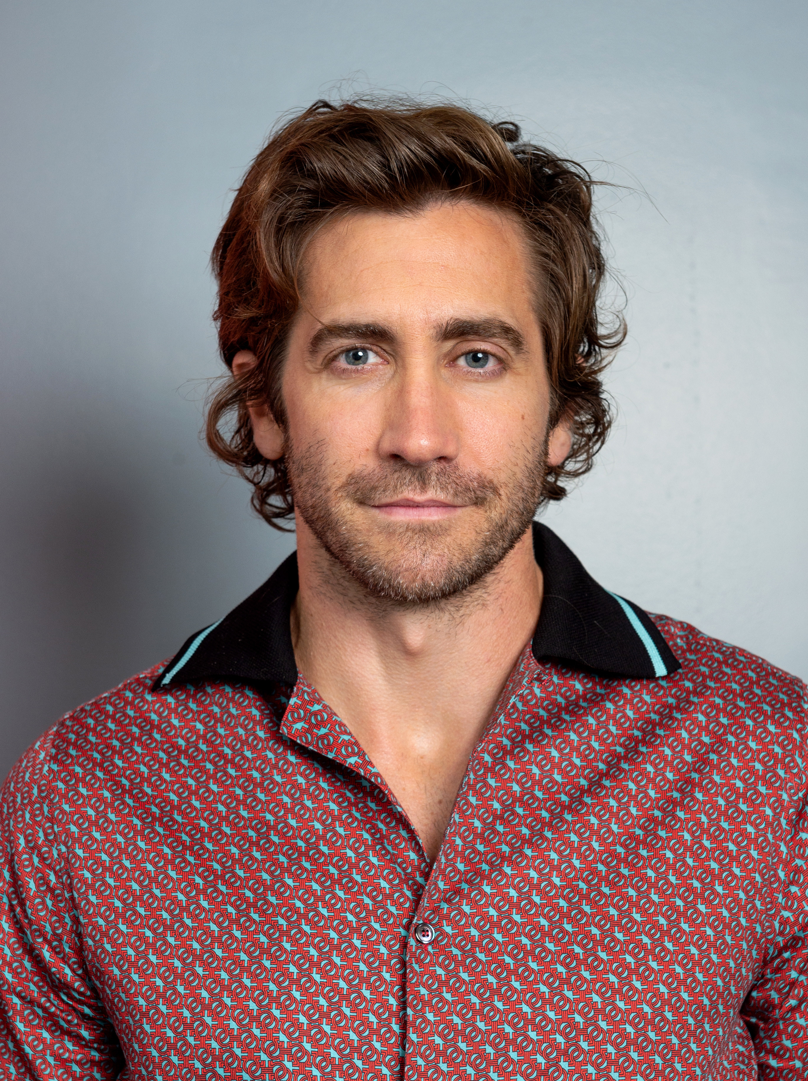 Gyllenhaal looks in the camera while wearing a collared button-down shirt