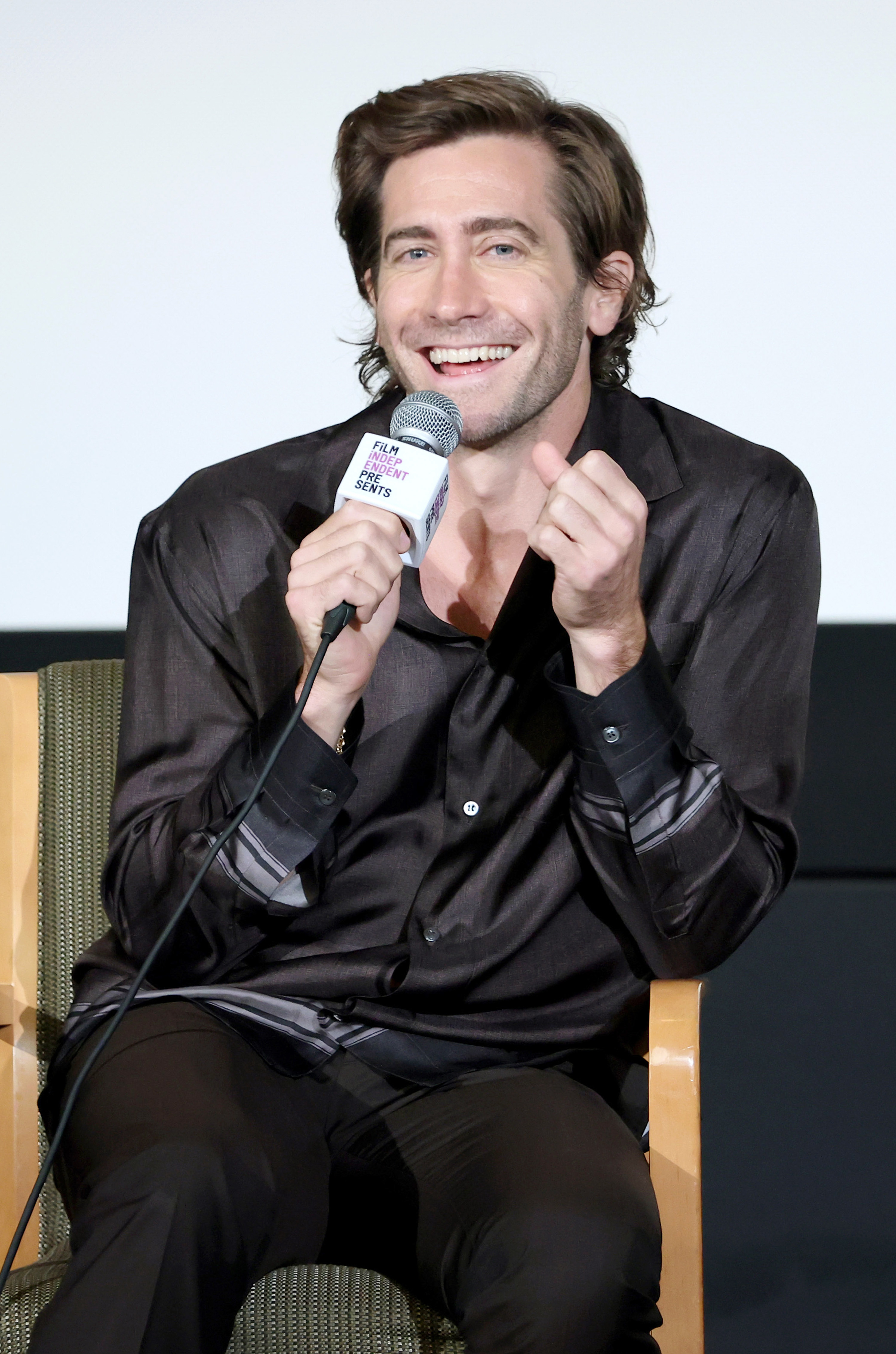 Gyllenhaal laughs while sitting in a chair and talking into a microphone
