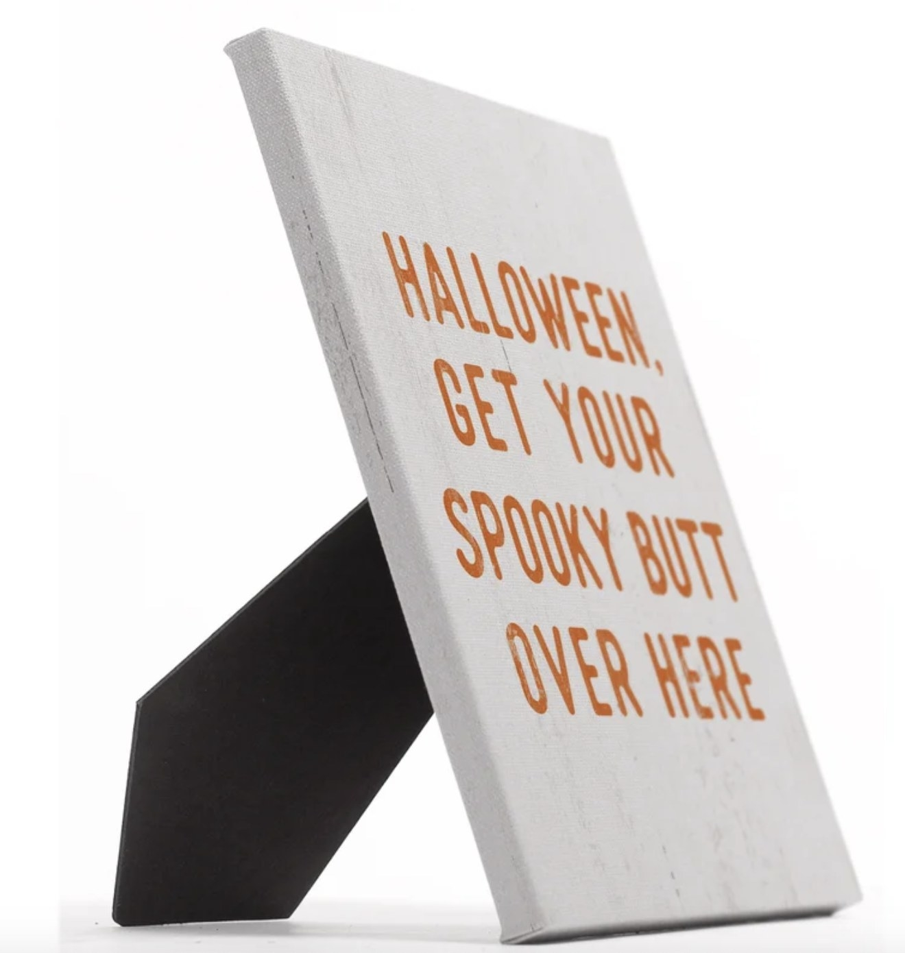 """The white sign says """"HALLOWEEN, GET YOUR SPOOKY BUTT OVER HERE"""" and has a black easel back"""